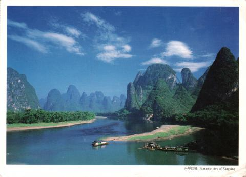 View of a river with boats, surrounded by mountains, in Xingping, China